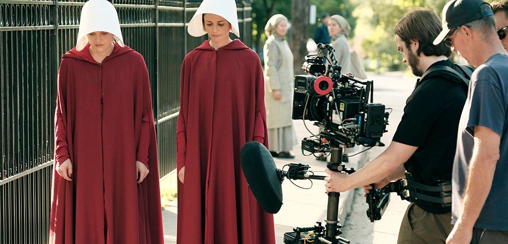 The Handmaidens Tale on set with 2 actresses walking down the set with camera men following to record the action