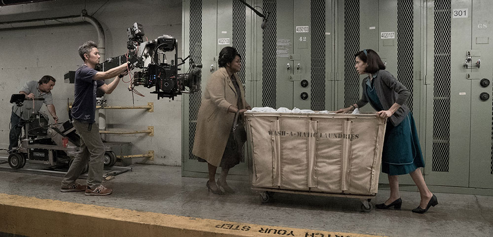 Two ladies on set with cameras and microphones wheeling a cart